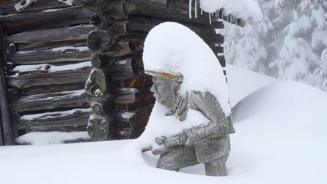 Verschneite Holzfigur im Schanfigg.