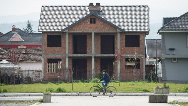 Ein halb fertiges Haus, ein Radfahrer fährt vorbei.