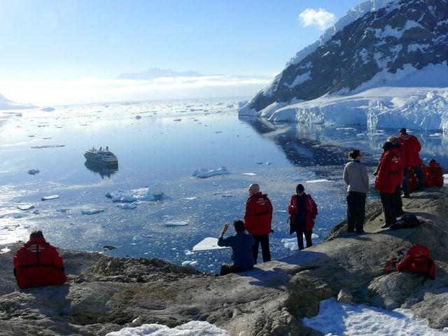 Im Vordergrund stehen Menschen in roten Daunenjacken auf einem Fels, dahinter eine Bucht mit dem grossen Schiff.