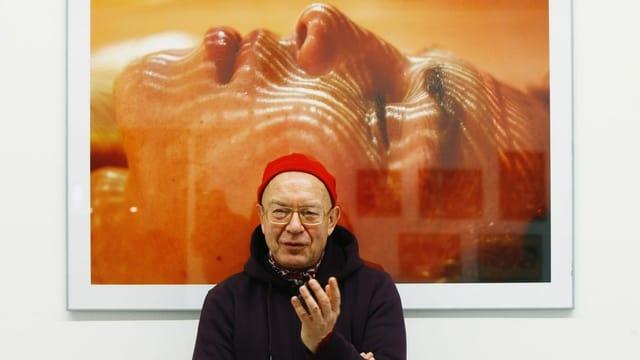 älterer Herr mit roter Mütze steht vor einer grossen Fotografie in Orangetönen.