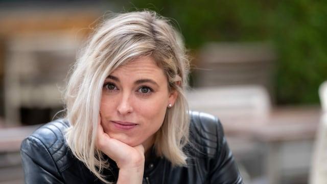eine junge blonde Frau schaut etwas nachdenklich in die Kamera
