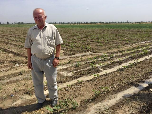 Habibulla Sharipov, ein Bauer, steht auf seinem Acker.