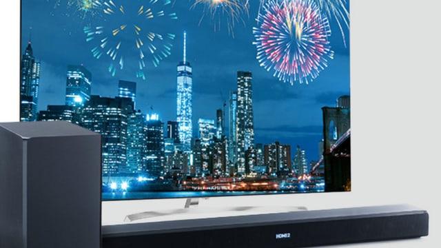 Soundbar vor einem Fernseher, auf dem ein Feuerwerk zu sehen ist.
