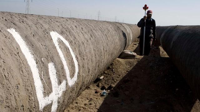 Ein Mann neben einer Gas-Pipeline.
