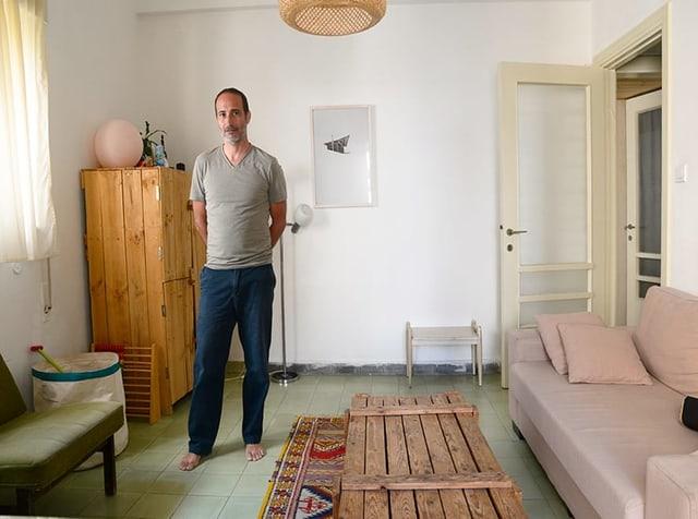 Ein Mann in blauen Hosen und grauem T-Shirt steht in einem Wohnzimmer.