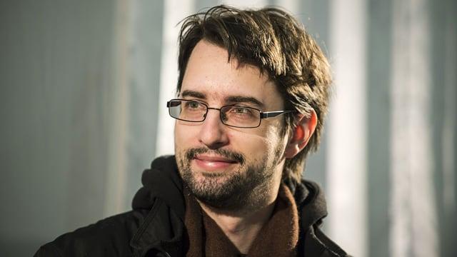 Ein Mann mit dunklen Haaren und Brille schaut in die Kamera.