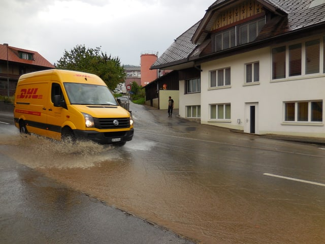 Ein DHL-Transporter fährt auf einer überfluteten Strasse. Das Wasser spritzt in alle Richtungen.
