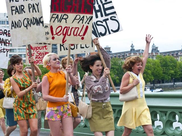 Frauen im schrillen 60er-Jahre-Look demonstrieren mit Plakaten auf einer Brücke.