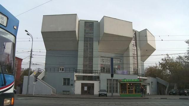 Ein Gebäude mit runder Form, mit eckigen Würfeln an der Aussenfassade.