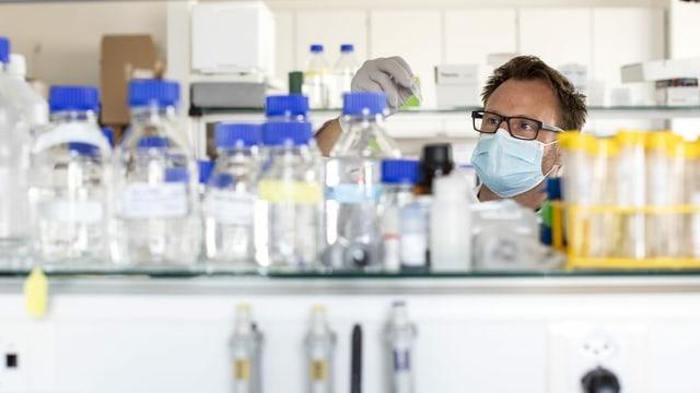 Ein Mann mit Mundschutz steht in einem Labor.