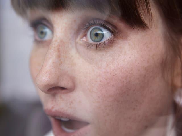 Eine Frau scheint erschrocken oder überrascht zu sein. Sie reisst die Augen auf und hat den Mund offen.