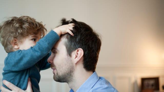 Ein kleiner Junge verwuschelt die Haare eines Mannes.