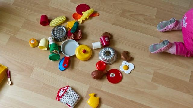 Spielzeug liegt am Boden, ein Kind - man sieht nur seine Beine, kriecht aus dem Bild.