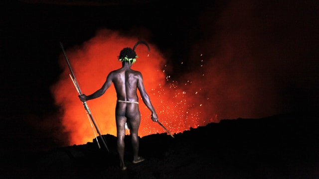 Mann steht vor ausbrechendem Vulkan.