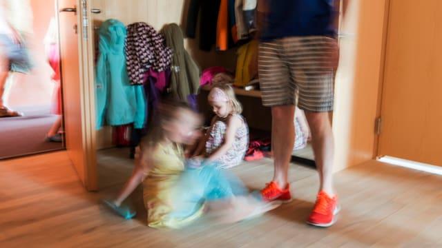 Symbolbild: Unscharfes Foto; zwei Kinder sitzen am Boden, daneben steht ein Mann in Shorts, der aber nur bis zur Brusthöhe erkennbar ist.