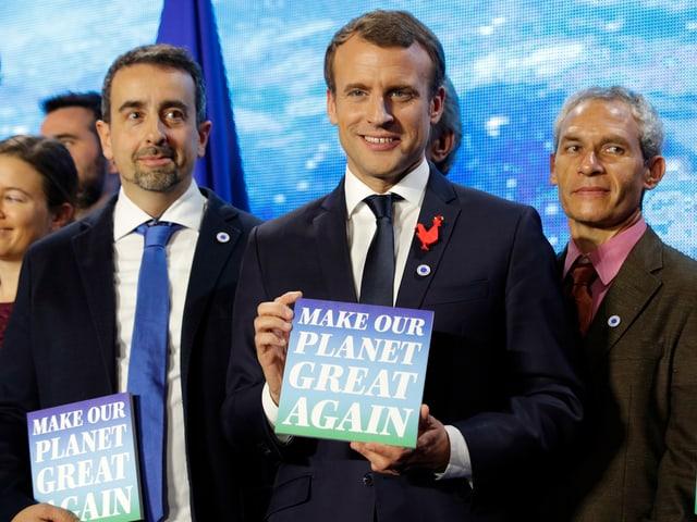 Macron mit einem Poster in der Hand.
