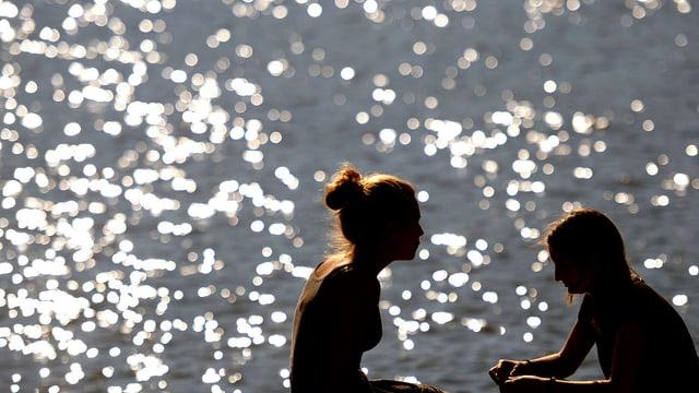 Zwei Mädchen sitzen vor dem Zürichsee.