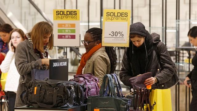 Winterlich angezogene Frauen betrachten Taschen im Ausverkauf in Frankreich.