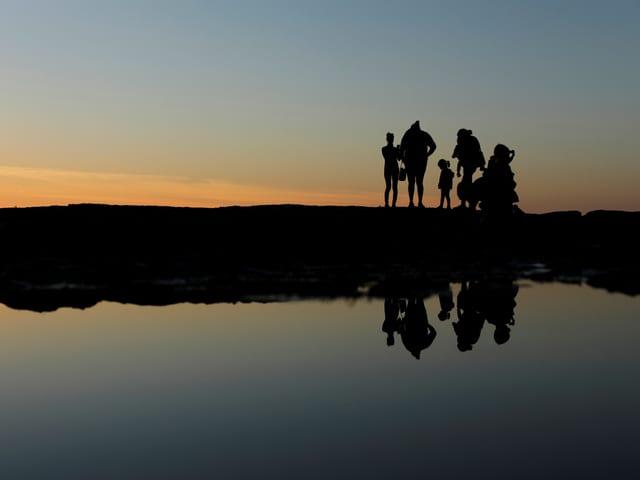 Familie bei Sonnenuntergang am Strand.