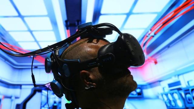 Ein Mann sitzt unter einer VR-Brille.