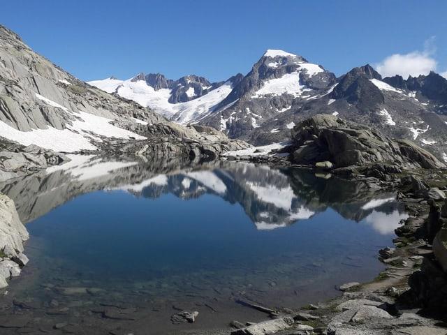 Gletschersee in den Alpen, bei strahlend blauem Himmel.