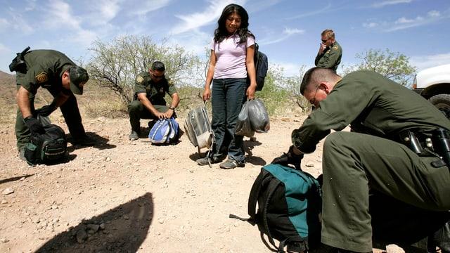 Grenzpolizisten kontrollieren Gepäck eines jungen Flüchtlings