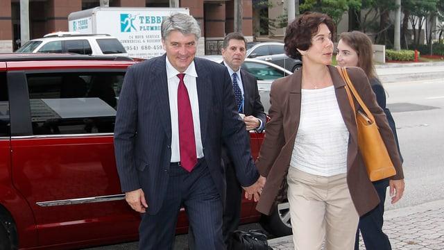 Raoul Weil und seine Ehefrau auf dem Gehsteig vor einem roten Auto, sie halten sich an der Hand.