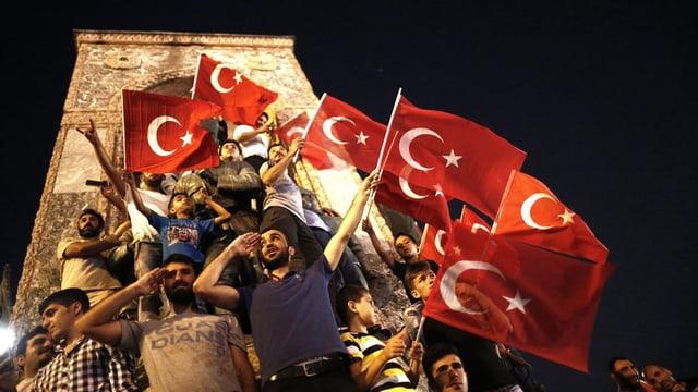 Umens e buobs stattan sco en ina sort piramida avant in monument sil la plazza Taksim ad Istanbul. Entgins tegnan lur maun al frunt per il salid militaric. Blers tegnan bandieras tircas.