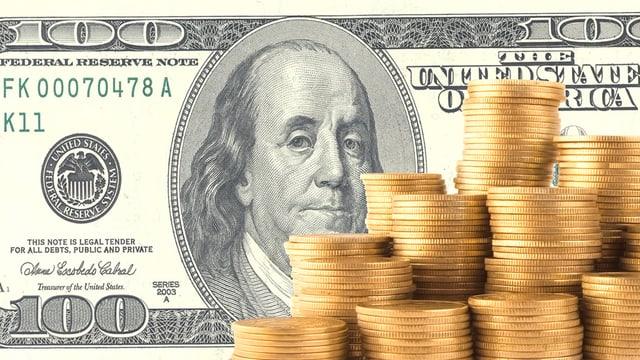 Eine 100-Dollar-Note, davor viele goldene Münzen.