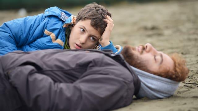 Ahmad und Amir Reza liegen am Strand.