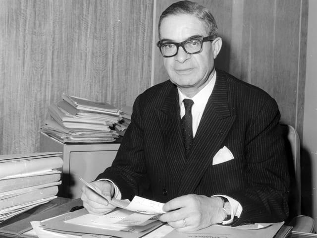Jean Rey auf einem Schwarzweiss-Bild sitzend an einem Schreibtisch