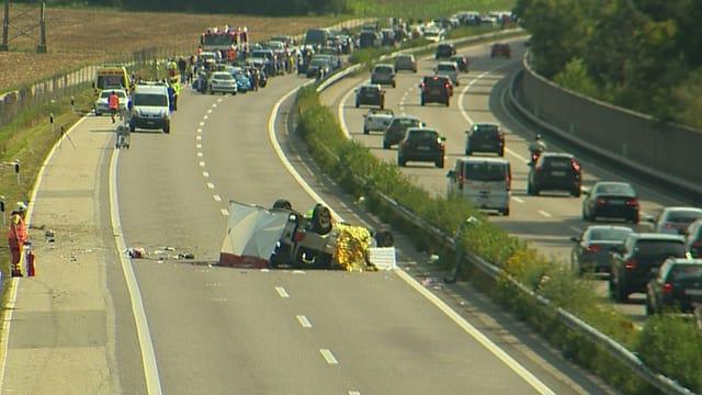 Unfallauto, auf dem Dach liegend. Mit einigem Abstand der gestaute Verkehr auf der A1.