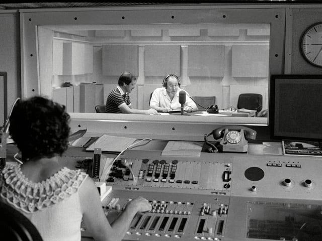 Hinter der Scheibe sitzen Ruedi Palm und Andreas Bitterlin. Die Technikerin ist von hinten sichtbar.