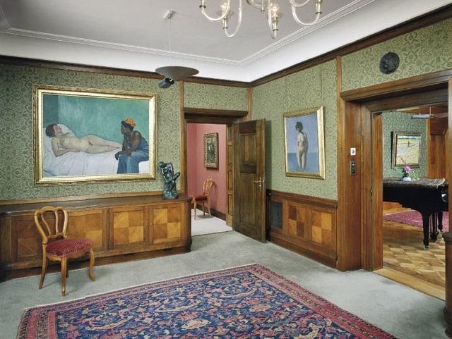 Ein Museumsraum mit grünen Wänden und Teppich.