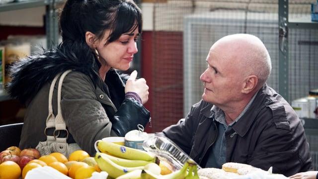 Ein Mann spricht mit einer weinenden Frau.