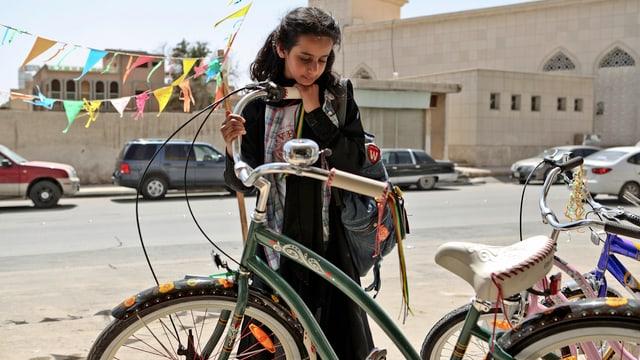 Das Mädchen Wadjda neben einem Fahrrad. Filmstill.