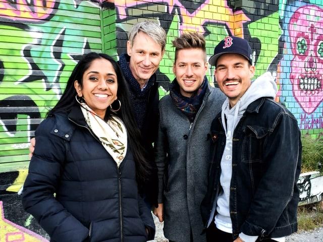 Tama Vakeesan steht mit ihren Gästen Franz Fischlin, Joël von Mutzenbecher und Fabian Zbinden vor einer Wand mit Grafitti.