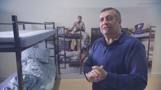 Mano Khalil steht in einem Flüchtlingszimmer mit Hochbetten.