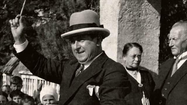 Mantegassi mit Dirigentenstab im Hintergrund lauschen Kinder und Erwachsene. Das Bild wurde wohl im Zürich der 40-er Jahre aufgenommen.