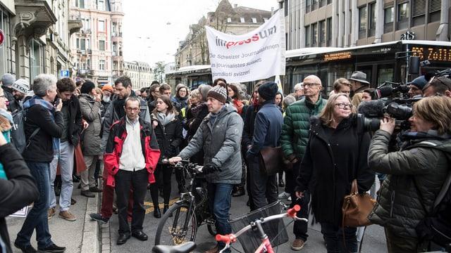 Personen mit TRansparenten auf der Strasse vor dem Redaktionsgebäude der SDA.