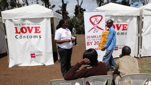 Helfer verteilen in Kenia gratis Kondome. Vor einem Zelt wartet ein Paar, das sich aus HIV testen lassen will.