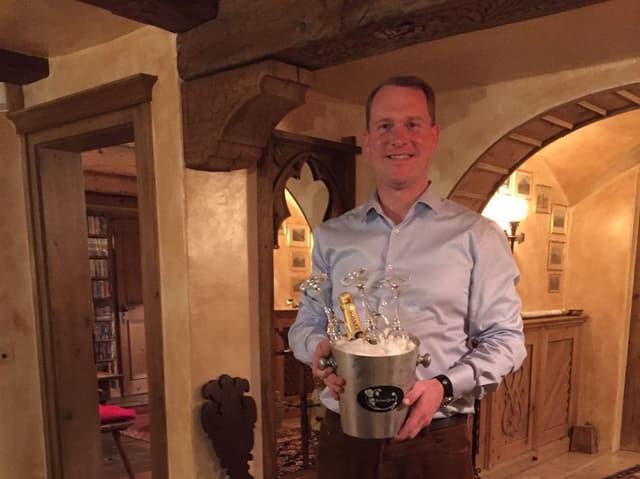 Der Butler Hanspeter Vochezer hält einen Eiskübel mit Champagnerflasche in Händen.
