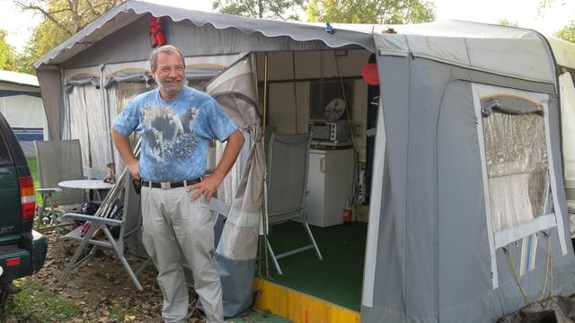 Ein Mann im T-Shirt vor einem Zelt