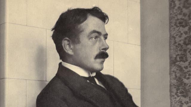 Schwarz-weiss-Foto von Robert Walser, wie er an eine Wand gelehnt auf einem Stuhl sitzt.