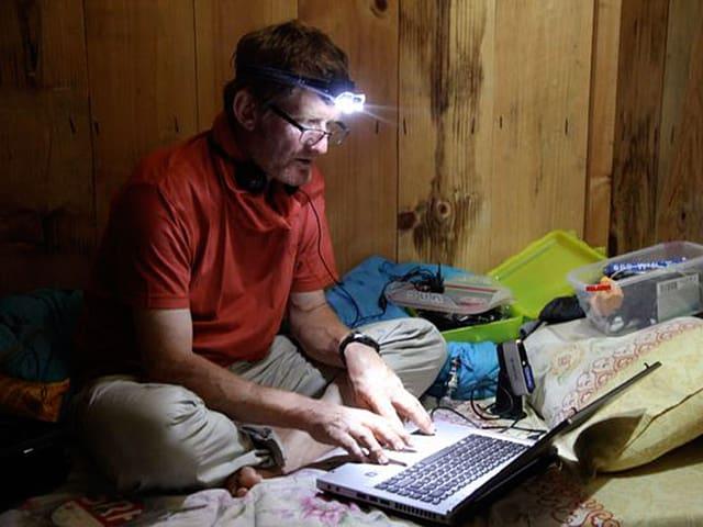 Tommy Dätwyler mit Stirnlampe am Computer.