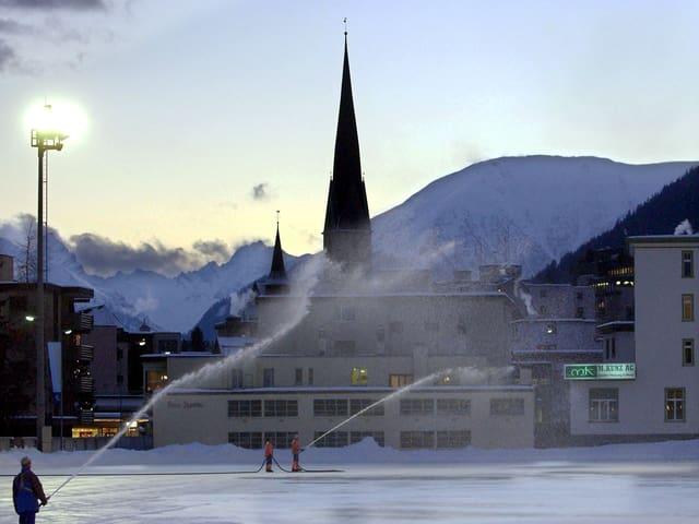 Häuser und Kirchturmspitze. Davor ein riesiges Eisfeld. Darauf stehen Menschen mit Schleuche. Sie spritzen Wasser in gigantischen Fontänen auf das Eis.