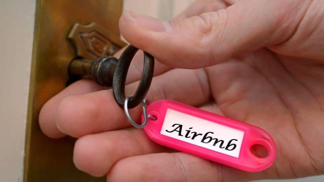 Eine Person dreht einen Schlüssel in einem Schloss