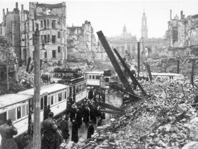 Strassenbahn inmitten von zerstörten Häusern.
