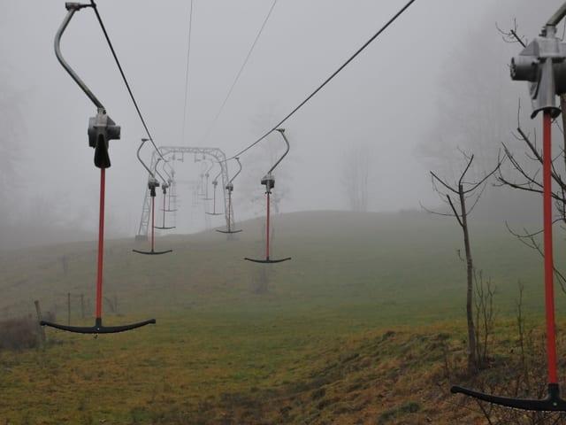 Ein Skilift im Nebel, alles ist nass, aber eben nicht weiss.