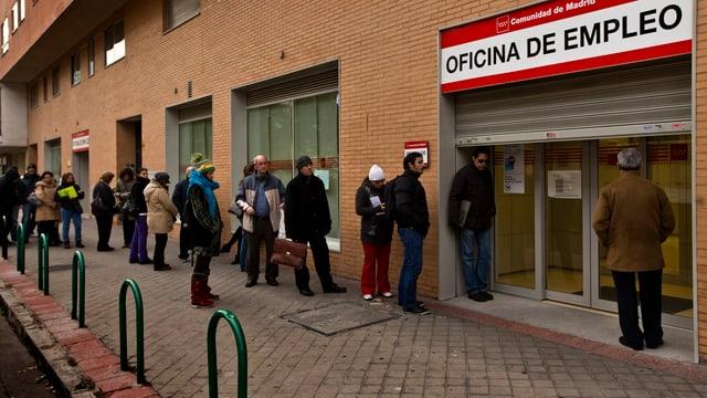 Menschen stehen in Spanien vor dem Arbeitsamt.